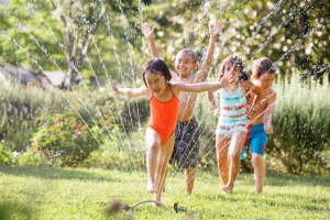 Children running through water sprinkler