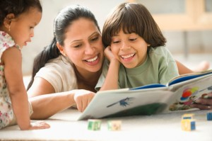 Hispanic mother laying on floor reading to children
